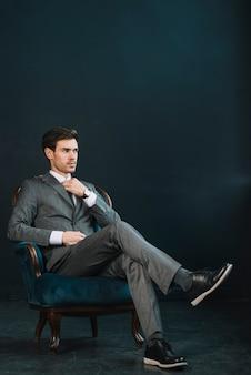 Giovane uomo d'affari alla moda che si siede sulla poltrona contro fondo scuro