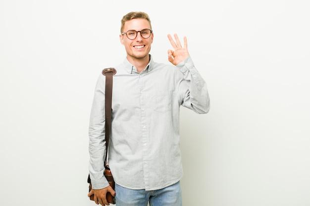 Giovane uomo d'affari allegro e fiducioso mostrando il gesto ok