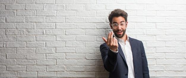 Giovane uomo d'affari amichevole invitando a venire, fiducioso e sorridente facendo un gesto con la mano, essere positivo e amichevole