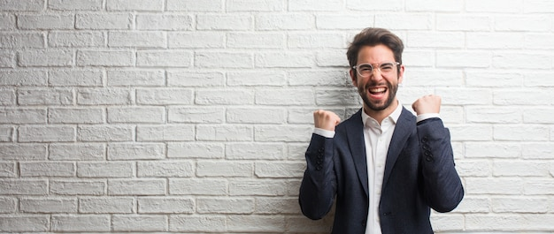 Giovane uomo d'affari amichevole molto felice ed emozionato, alzando le braccia, celebrando una vittoria o successo, vincendo la lotteria