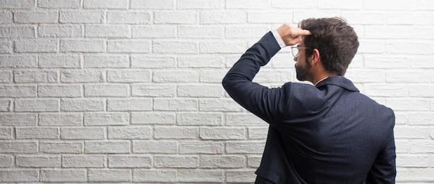 Giovane uomo d'affari amichevole mostrando indietro, in posa e in attesa, guardando indietro