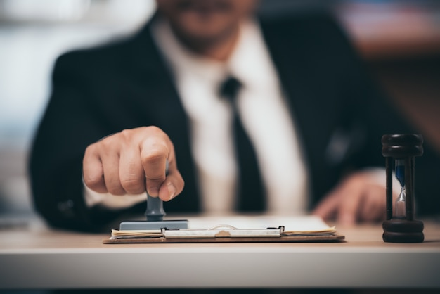 Giovane uomo d'affari appoval timbro timbro sul contratto di lavoro di carta, prestito denaro approvato.
