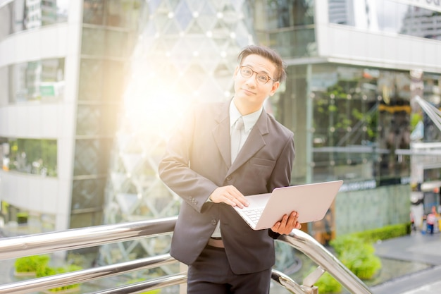 Giovane uomo d'affari asia in tuta con il suo computer portatile all'aperto, moderno edificio sullo sfondo