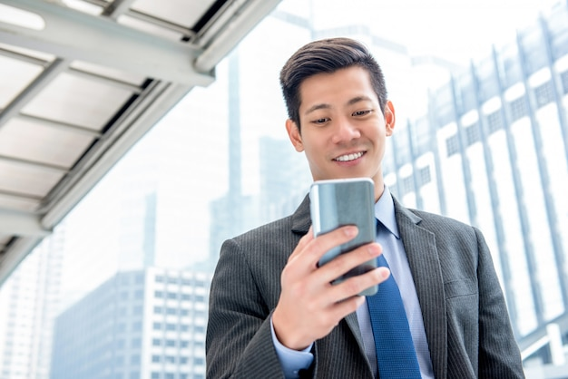 Giovane uomo d'affari asiatico bello che per mezzo del telefono cellulare all'aperto