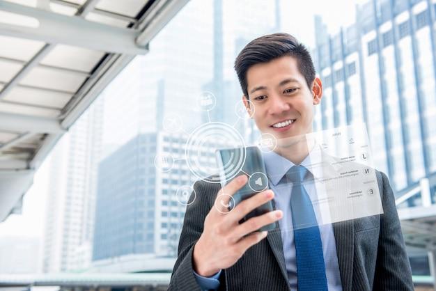 Giovane uomo d'affari asiatico bello che per mezzo del telefono cellulare con la visualizzazione di schermo virtuale