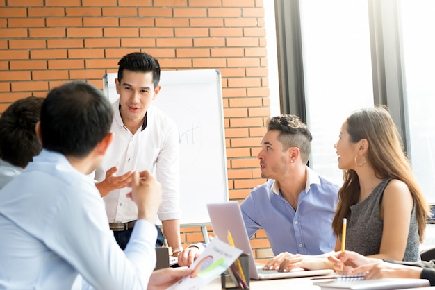 Giovane uomo d'affari asiatico casuale che presenta il suo lavoro nella riunione