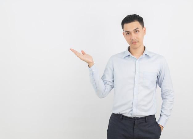 Giovane uomo d'affari asiatico che indica con un dito per presentare un prodotto o un'idea