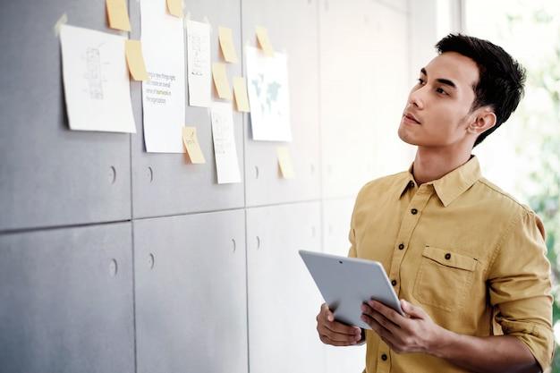 Giovane uomo d'affari asiatico che lavora alla compressa digitale nella sala riunioni dell'ufficio. uomo che analizza i piani e il progetto di dati