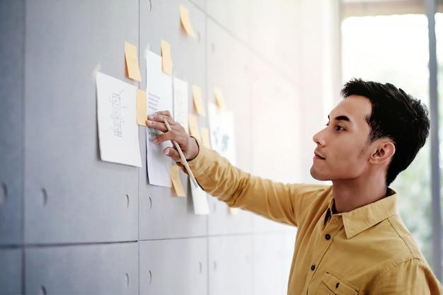 Giovane uomo d'affari asiatico che lavora nella sala riunioni dell'ufficio. concentrarsi sulla nota del documento al muro. uomo che analizza i piani e il progetto di dati
