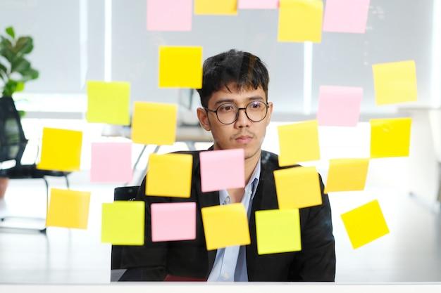 Giovane uomo d'affari asiatico che pensa mentre leggendo le note appiccicose all'ufficio, idee di piallatura creative di brainstoming di affari a successo nell'affare
