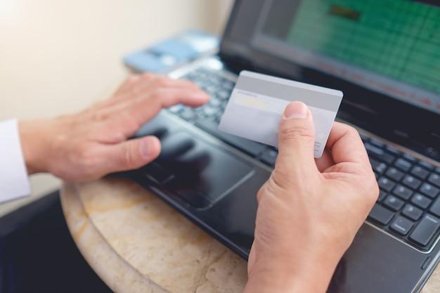 Giovane uomo d'affari asiatico che si siede con il computer portatile e che tiene paga della carta di credito per lo shopping online