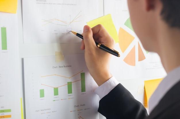 Giovane uomo d'affari asiatico che usando il lavoro della penna che analizza i documenti finanziari sulla lavagna