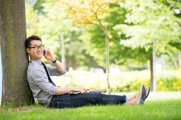 Giovane uomo d'affari asiatico che utilizza compressa, telefono cellulare nel parco
