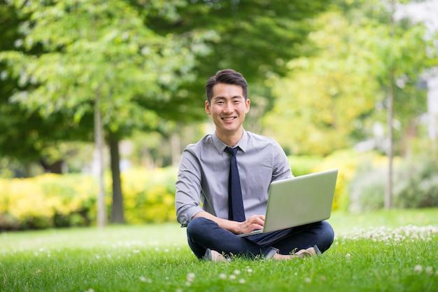 Giovane uomo d'affari asiatico & di successo che utilizza compressa, computer portatile, telefono cellulare nel parco
