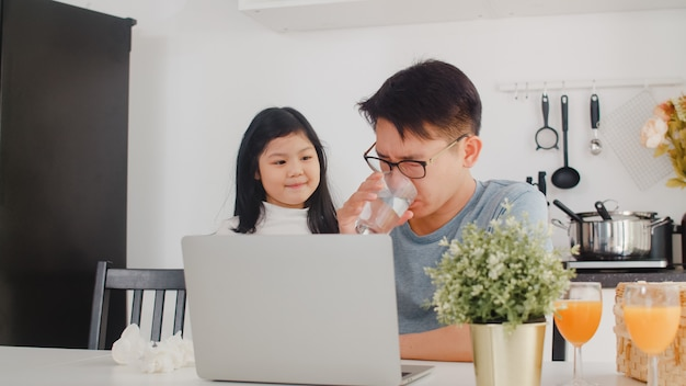 Giovane uomo d'affari asiatico serio, stress, stanco e malato mentre si lavora al computer portatile a casa. giovane figlia che consola suo padre che lavora duramente nella cucina moderna a casa la mattina.