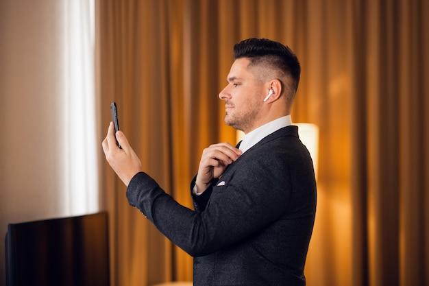 Giovane uomo d'affari attraente che prende un selfie sul suo smartphone, mentre riparando la sua cravatta
