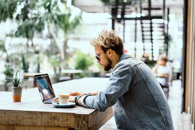 Giovane uomo d'affari attraente in un caffè lavora per un laptop, beve caffè.