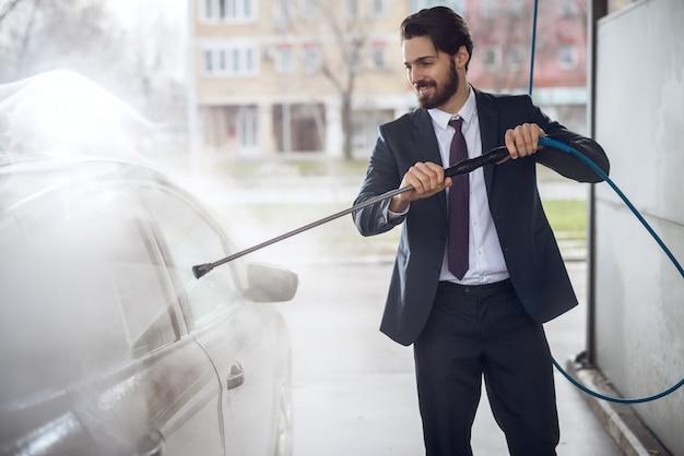 Giovane uomo d'affari barbuto alla moda soddisfatto allegro bello nel vestito che pulisce l'automobile con una pistola a acqua nella stazione di lavaggio di self service manuale.