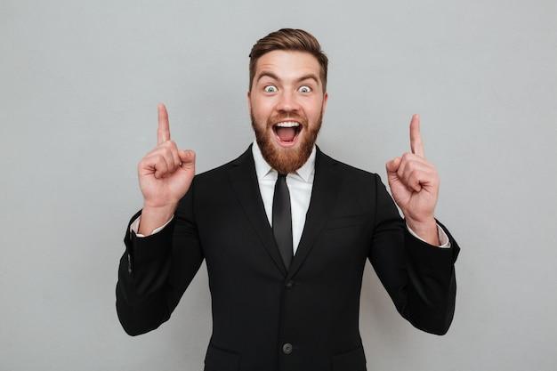 Giovane uomo d'affari barbuto emozionante che ha un'idea