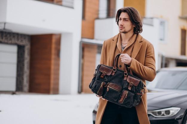 Giovane uomo d'affari bello che cammina fuori dalla casa alla sua automobile