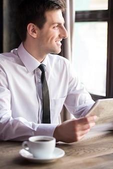 Giovane uomo d'affari bello che legge il giornale.