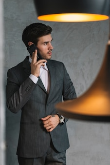 Giovane uomo d'affari bello che parla sul cellulare
