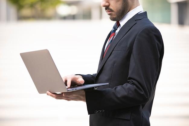 Giovane uomo d'affari bello che propone con il computer portatile