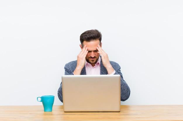 Giovane uomo d'affari bello che sembra stressato e frustrato, lavorando sotto pressione con mal di testa e turbato da problemi