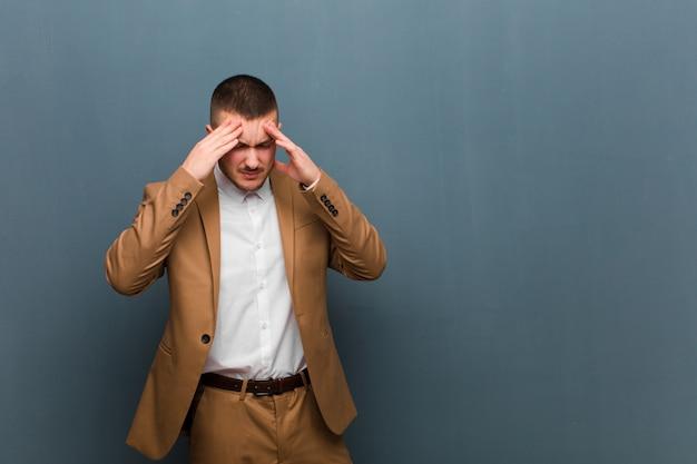 Giovane uomo d'affari bello che sembra stressato e frustrato, lavorando sotto pressione con un mal di testa e travagliato da problemi contro la parete piatta