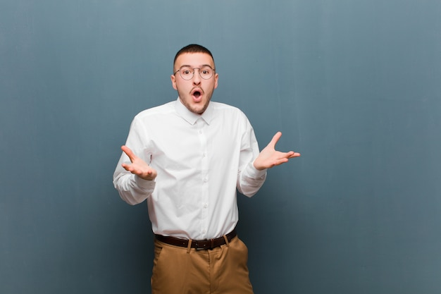 Giovane uomo d'affari bello che si sente estremamente scioccato e sorpreso, ansioso e in preda al panico, con uno sguardo stressato e inorridito contro il muro piatto