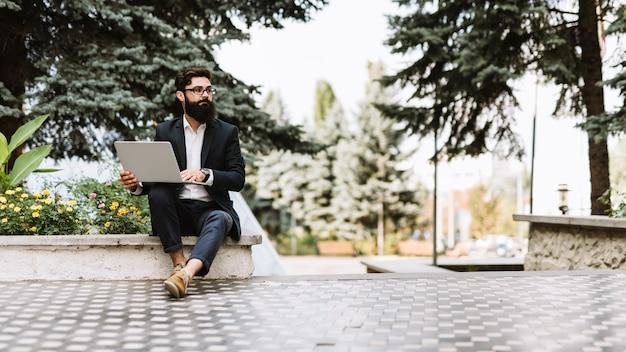 Giovane uomo d'affari bello che si siede con il computer portatile nel parco che osserva via
