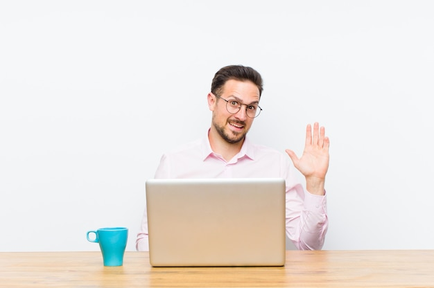 Giovane uomo d'affari bello che sorride allegramente e allegramente, agitando la mano, dandovi il benvenuto e salutandovi, o salutandovi