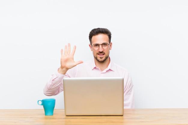 Giovane uomo d'affari bello che sorride e che sembra amichevole, mostrando numero cinque