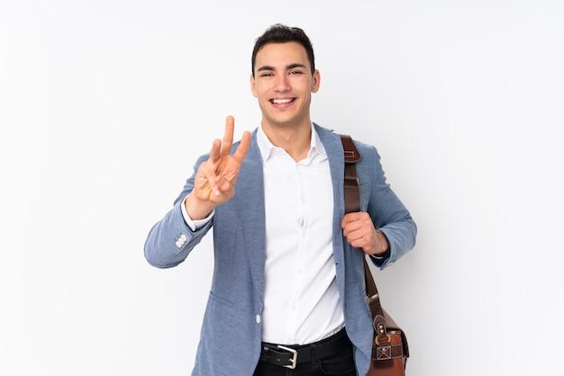 Giovane uomo d'affari bello sulla parete felice e contando tre con le dita