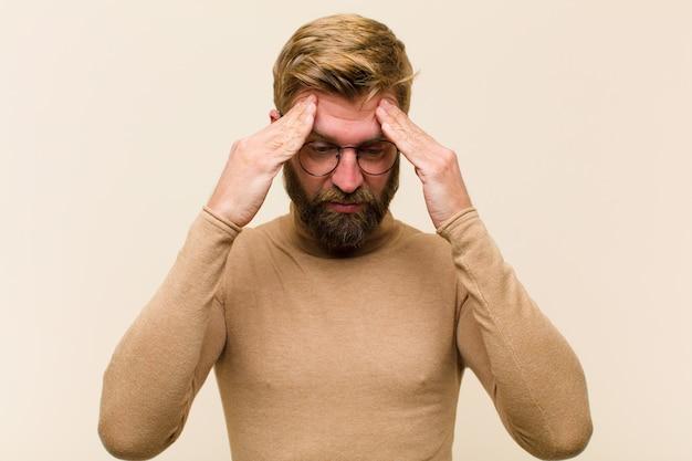 Giovane uomo d'affari biondo che sembra stressato e frustrato, che lavora sotto pressione con un mal di testa e turbato da problemi