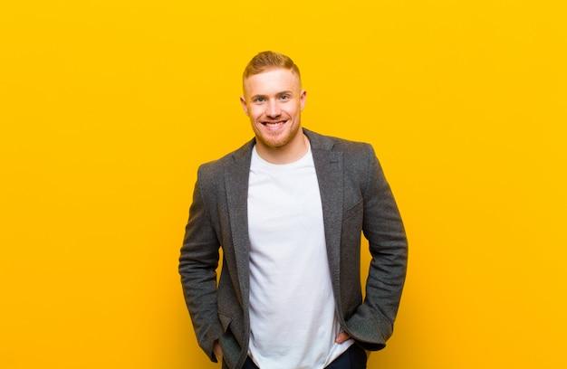 Giovane uomo d'affari biondo che sorride allegramente e casualmente con un'espressione positiva, felice, sicura e rilassata
