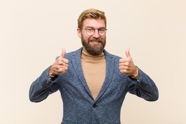 Giovane uomo d'affari biondo che sorride ampiamente sembrando felice, positivo, sicuro e riuscito, con entrambi i pollici in su
