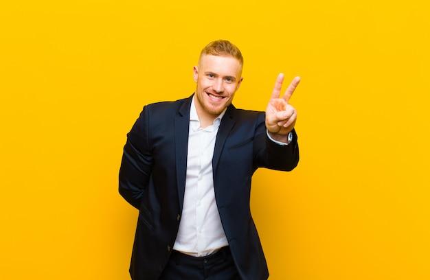 Giovane uomo d'affari biondo che sorride e sembra felice, spensierato e positivo, gesticolando vittoria o pace con una mano