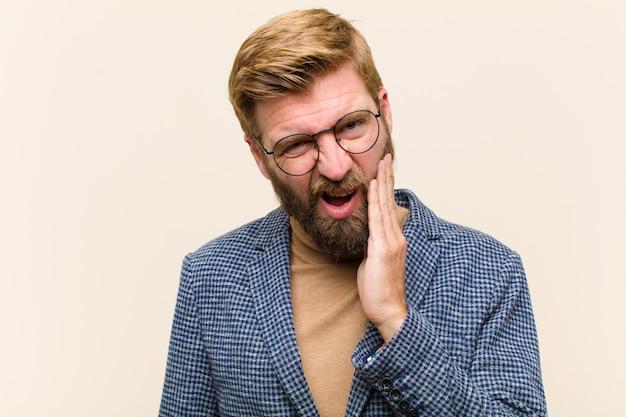 Giovane uomo d'affari biondo che tiene la guancia e che soffre di mal di denti doloroso, sentirsi male, miserabile e infelice, in cerca di un dentista