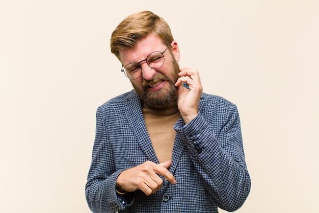 Giovane uomo d'affari biondo sentirsi stressato, frustrato e stanco, sfregando il collo doloroso, con uno sguardo preoccupato e turbato