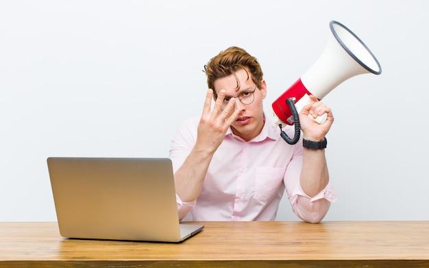 Giovane uomo d'affari capo rosso che lavora nel suo scrittorio con un megafono