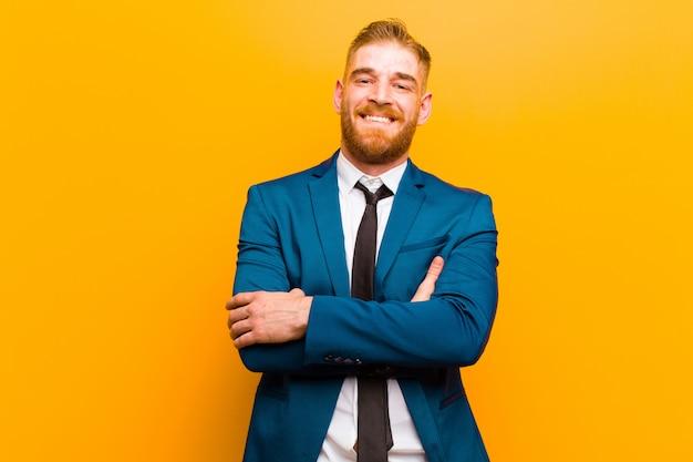 Giovane uomo d'affari capo rosso che ride felicemente con le braccia attraversate, con una posa rilassata, positiva e soddisfatta contro l'arancio