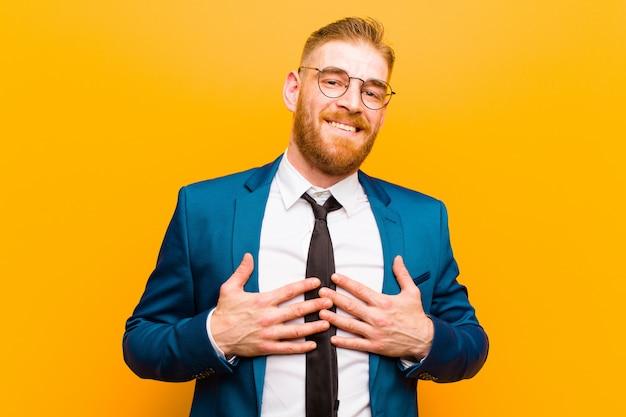 Giovane uomo d'affari capo rosso che sembra felice, sorpreso, fiero ed eccitato, indicando se stesso sull'arancia