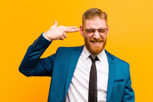 Giovane uomo d'affari capo rosso che sembra infelice e sollecitato, gesto di suicidio che fa il segno della pistola con la mano, indicante la testa contro l'arancia