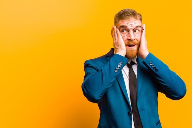 Giovane uomo d'affari capo rosso sentirsi felice, eccitato e sorpreso, guardando al lato con entrambe le mani sul viso contro l'arancia
