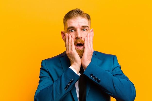 Giovane uomo d'affari capo rosso sentirsi scioccato e spaventato, guardando terrorizzato con la bocca aperta e le mani sulle guance contro l'arancia