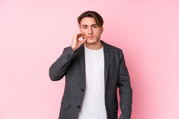Giovane uomo d'affari caucasico in posa isolato con le dita sulle labbra mantenendo un segreto.