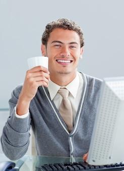 Giovane uomo d'affari che beve un caffè al suo scrittorio