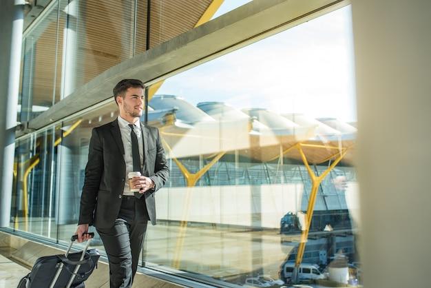 Giovane uomo d'affari che cammina al terminal dell'aeroporto con bagagli che sorride con un caffè