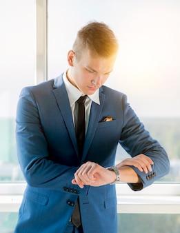 Giovane uomo d'affari che controlla il tempo sull'orologio
